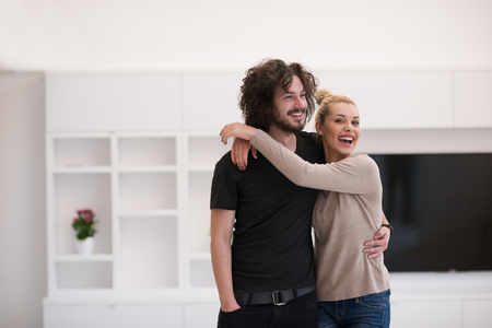 pareja en casa: Portrait of a happy young beautiful couple hugging in their new home