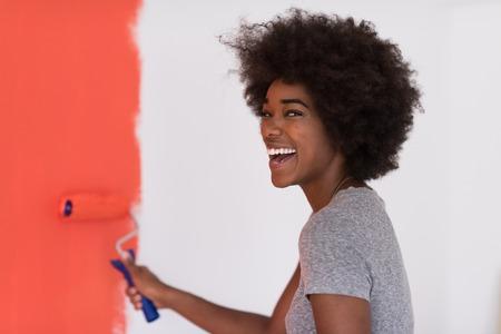 Portret van een jonge mooie Afrikaanse Amerikaanse vrouw schilderende muur in haar nieuwe appartement Stockfoto