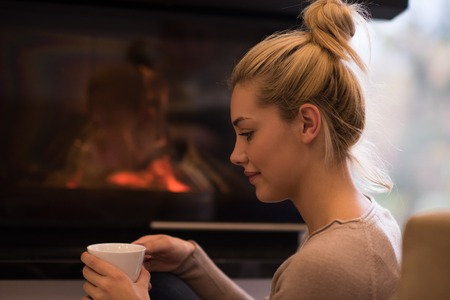 Happy joyful woman drinking cup of coffee relaxing at fireplace. Young beautiful girl with hot beverage heating warming up. autumn at home.