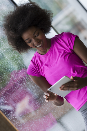 rain weather: beautiful african american woman using tablet computer from home while rain and bad weather is outdoor