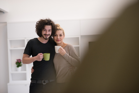 newly wedded couple: Portrait of a happy young beautiful couple hugging and drinking coffee in their new home
