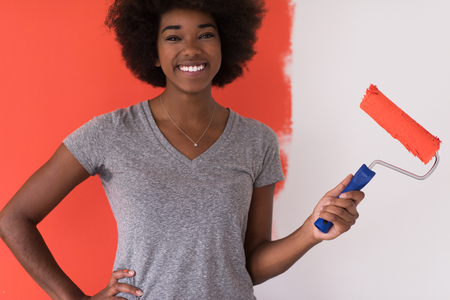 domiciles: portrait of a young beautiful African American woman painting wall in her new apartment