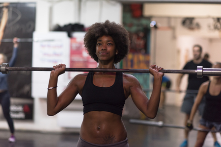 american sport: Young Cute african american sport woman in fitness room lifting empty bar