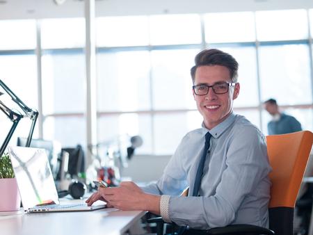 Jeune entrepreneur pigiste travaillant dans un ordinateur portable dans coworking espace Banque d'images - 79343611