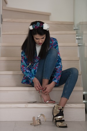 luxury apartment: portrait of a young beautiful woman on the stairs in her luxurious home