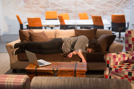 exhausting: A young casual businessman sleeping on a sofa during a work break in a creative office