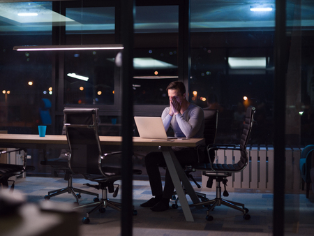 koncentrovaný: Mladý muž pracující na notebooku v noci v temné kanceláři. Návrhář pracuje později. Reklamní fotografie
