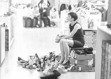 Woman Chooses  Shoes At Fashionable Shop Imagens