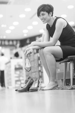 Woman Chooses  Shoes At Fashionable Shop Banco de Imagens