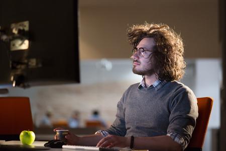 koncentrovaný: Unavený podnikatel pracující pozdě v práci přesčas v kanceláři v noci pití kávy pokračovat.