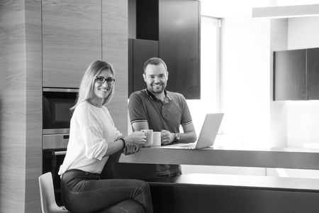 luxury apartment: Young couple drinking coffee and using laptop computer at luxury home together, looking at screen, smiling. Stock Photo