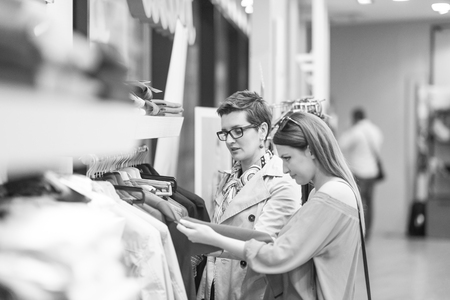 Two Girl-Friends On Shopping Walk On Shopping Centre With Bags And Choosing Stock Photo