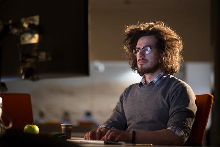 koncentrovaný: Mladý muž pracující na počítači v noci v temné kanceláři. Návrhář pracuje později.