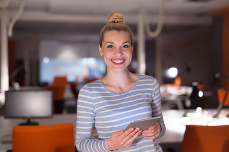 stay beautiful: young female entrepreneur working on digital tablet in night office Stock Photo