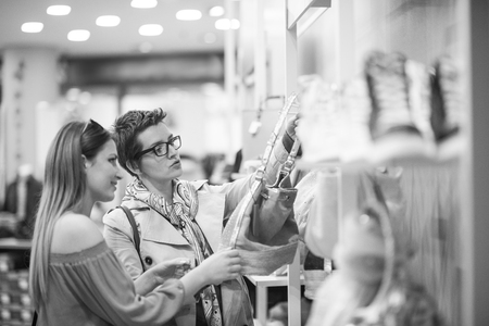 shopper: Two Girl-Friends On Shopping Walk On Shopping Centre With Bags And Choosing Stock Photo