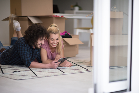 websurfing: Young couple in love moving in a new flat, lying on the floor and surfing the web on a tablet computer in search of new redecoration ideas Stock Photo