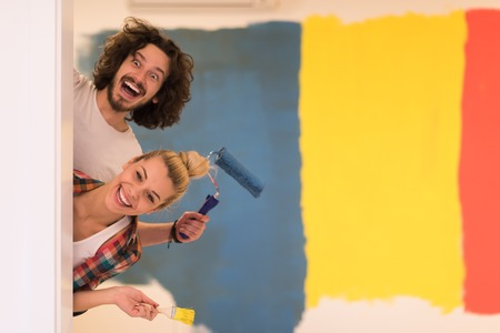 portrait of happy smiling young couple painting interior wall of new house  peeking from behind the wall Stock Photo
