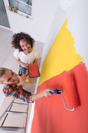 home decorating: happy smiling young couple painting interior wall of new house Stock Photo