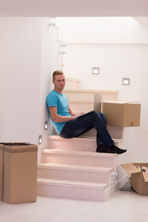 Happy young man sitting in stairway at home, using laptop computer with boxes around him Stock Photo