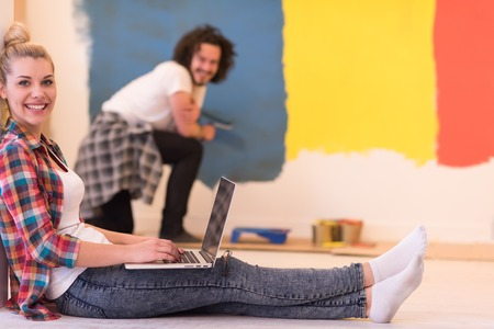 home decorating: Happy couple doing home renovations, the man is painting the room and the woman is relaxing on the floor and connecting with a laptop Stock Photo