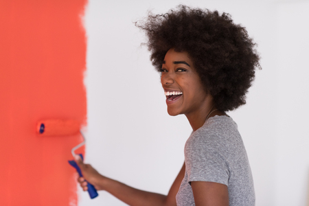 home decorating: portrait of a young beautiful African American woman painting wall in her new apartment