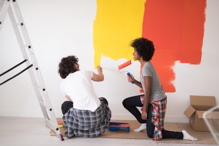 home decorating: happy young multiethnic couple painting interior wall of new house Stock Photo