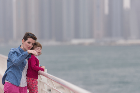 young mother and cute little girl running and cheerfully spend their time on the promenade by the sea with a big city in the background Stock Photo
