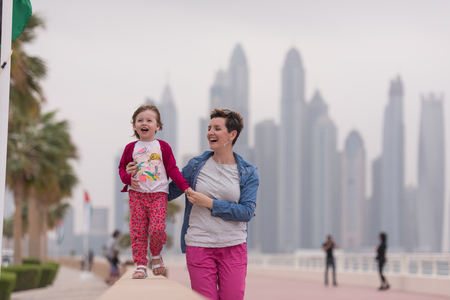 young mother and cute little girl running and cheerfully spend their time on the promenade by the sea with a big city in the background Фото со стока