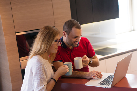 Young couple drinking coffee and using laptop computer at luxury home together, looking at screen, smiling. Stock Photo