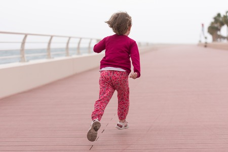 cute little girl running and cheerfully spend her time on the promenade by the sea
