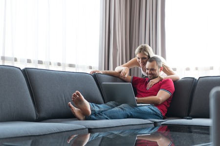 Young couple using laptop computer at luxury home together, looking at screen, smiling. Stock Photo