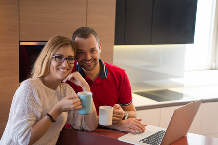 snug: Young couple drinking coffee and using laptop computer at luxury home together, looking at screen, smiling. Stock Photo