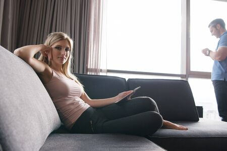 domicile: Blonde Woman Sitting On A Sofa Using Her Tablet