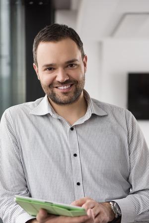 Homme d'affaires utilisant la tablette numérique dans le bureau d'entreprise par fenêtre Banque d'images - 81566323