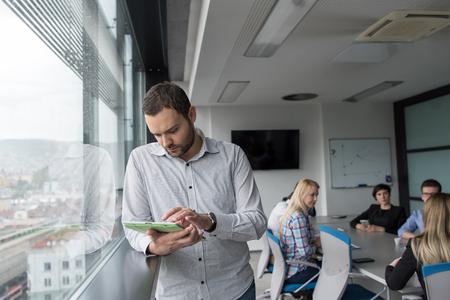 Homme d'affaires utilisant la tablette numérique dans le bureau d'entreprise par fenêtre Banque d'images - 81571982