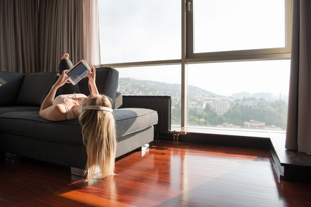 woman listening to music with sun flare coming from window of apartment