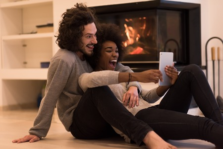 beautiful young multiethnic couple using tablet computer on the floor of their luxury home in front of fireplace at autumn day