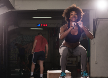 Fit young african american woman box jumping at a crossfit style gym. Female athlete is performing box jumps at gym. Stock Photo