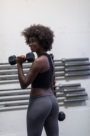 young beautiful African American woman doing bicep curls in a gym 版權商用圖片