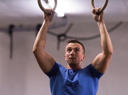 Fitness handsome man doing dipping exercise using rings in the gym Stock Photo - 81598651