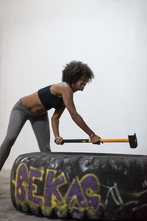 Sledgehammer Tire Hits african american woman workout at gym with hammer and tractor tire Banco de Imagens