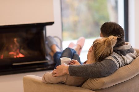 젊은 로맨틱 커플 벽난로 집 앞의 소파에 앉아, 서로를 찾고 얘기 하 고 커피를 마시는가 날