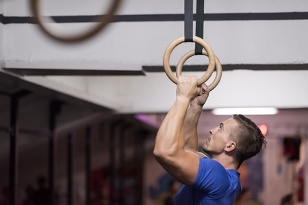 Fitness handsome man doing dipping exercise using rings in the gym