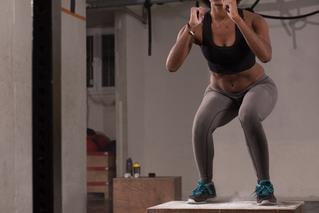 Fit young african american woman box jumping at a crossfit style gym. Female athlete is performing box jumps at gym with focus on legs