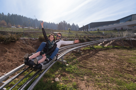 Excited young couple enjoys driving on alpine coaster Stock Photo - 82663350