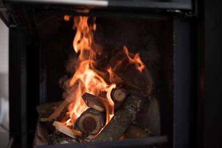 美しい炎の暖炉。ガラス扉付けモダンな暖炉の薪の明るい炎