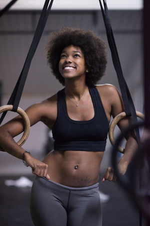 Fitness dip ring african american young woman relaxed after workout at gym dipping exercise Stock Photo