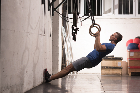 Fitness handsome man doing dipping exercise using rings in the gym Stock Photo - 81691524