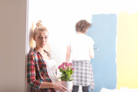 home decorating: Happy couple doing home renovations, the man is painting the room and the woman hold the pot with flowers