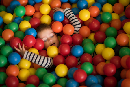 hundreds: Young boy having fun and hiding in hundreds of colorful plastic balls